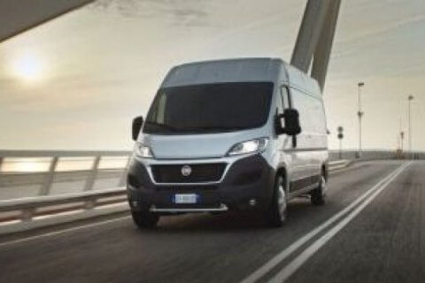 Bus marki Fiat nowy lub po serwisie jadący mostem, nowoczesną drogą
