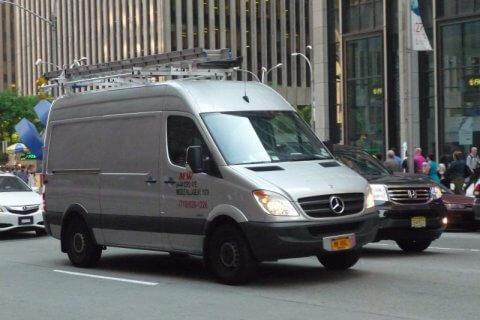 Naprawiony bus dostawczy marki Mercedes jadący ulicą miasta
